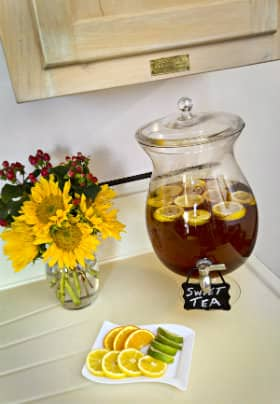 Small vase of yellow sunflowers, glass dispenser with iced tea with lemons and square white plate of lemons and limes