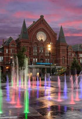 Large red brick historic building sitting behind water fountains in colors of pink, purple and green