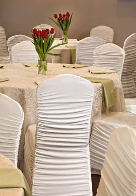 Round tables with tan lace table cloths, white covered chairs and an arrangement of red tulips on the table