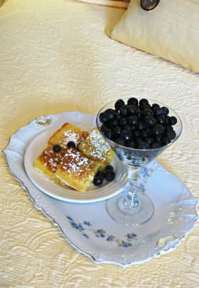 White rectangular china plate with blue flowers, a plate of lemon bars and dish of blueberries