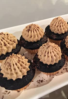 White rectangular plate with seven small chocolate cupcakes with chocolate icing sprinkled with pieces of shaved chocolate