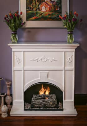 Brown wood fireplace with burning orange and yellow fire with a vase of yellow and pink flowers on mantel