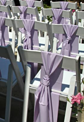Four rows of white chairs decorated with a pale purple bow tied to the back of the chair