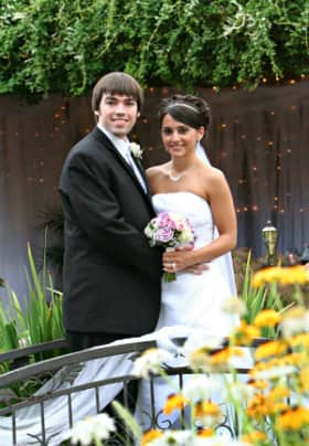Bride with purple flower arrangement and groom standing on an iron bridge in front of yellow flowers