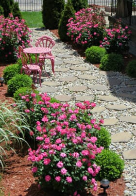 White rock and stone walkway surrounded by pink rosebushes on each side and a pink table & chairs on walkway