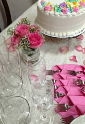 White table with white iced cake and pastel colored flowers, arrangement of pink roses and clear glasses