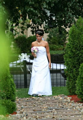 Bride in a white dress with purple flowers walking down a stone bathway surrounded by tall evergreen bushes
