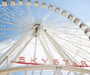 large white ferris wheel with gondolas attached