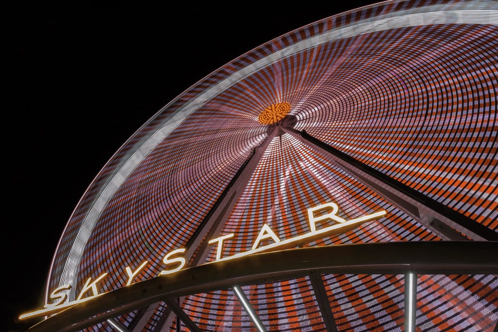 Large round ferris wheel with red and gray lights and the words SKYSTAR