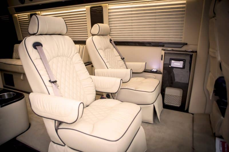 Two white armchair seats with black trim inside of Limousine