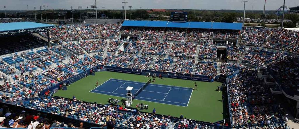 Tennis stadium filled with people watching two players on blue tennis court
