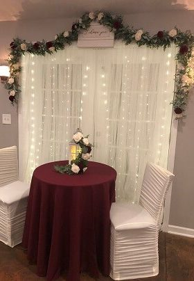 Table for two with burgundy table cloth and lighted white curtain background