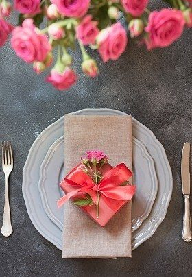 White plates with silverware topped with peach napkin wrapped in a peach bow