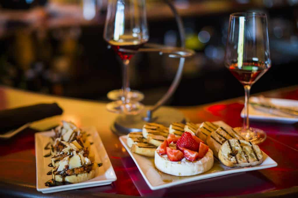 Two white plates with small bites of food, red strawberries and two glasses of white wine