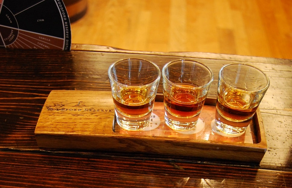 Three glasses half full of amber bourbon sitting on a wooden rectangular plate