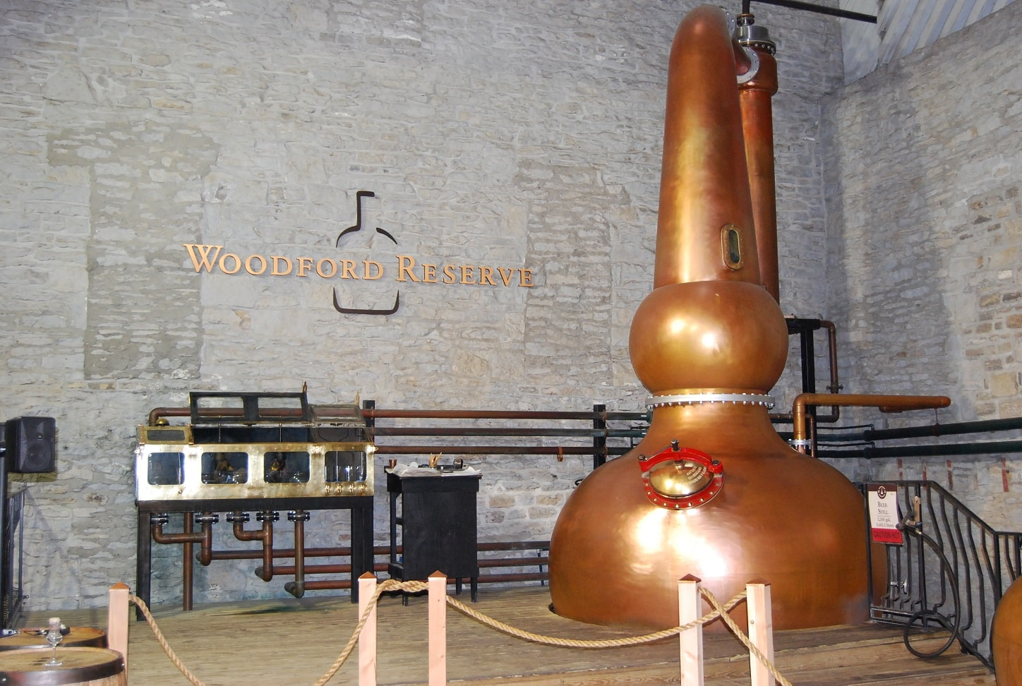 "Large copper bottle shaped tank sitting on a wood floor in front of brick wall that says ""Woodford Reserve"""