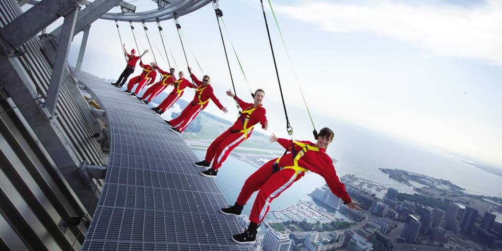 seven people in red suits suspended by harnesses over the top of a city